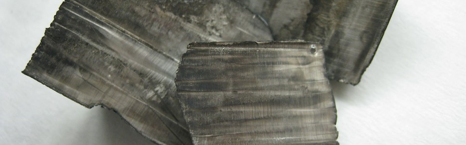 Lithium pellets covered in white lithium hydroxide (left) and ingots with a thin layer of black nitride tarnish (right)
